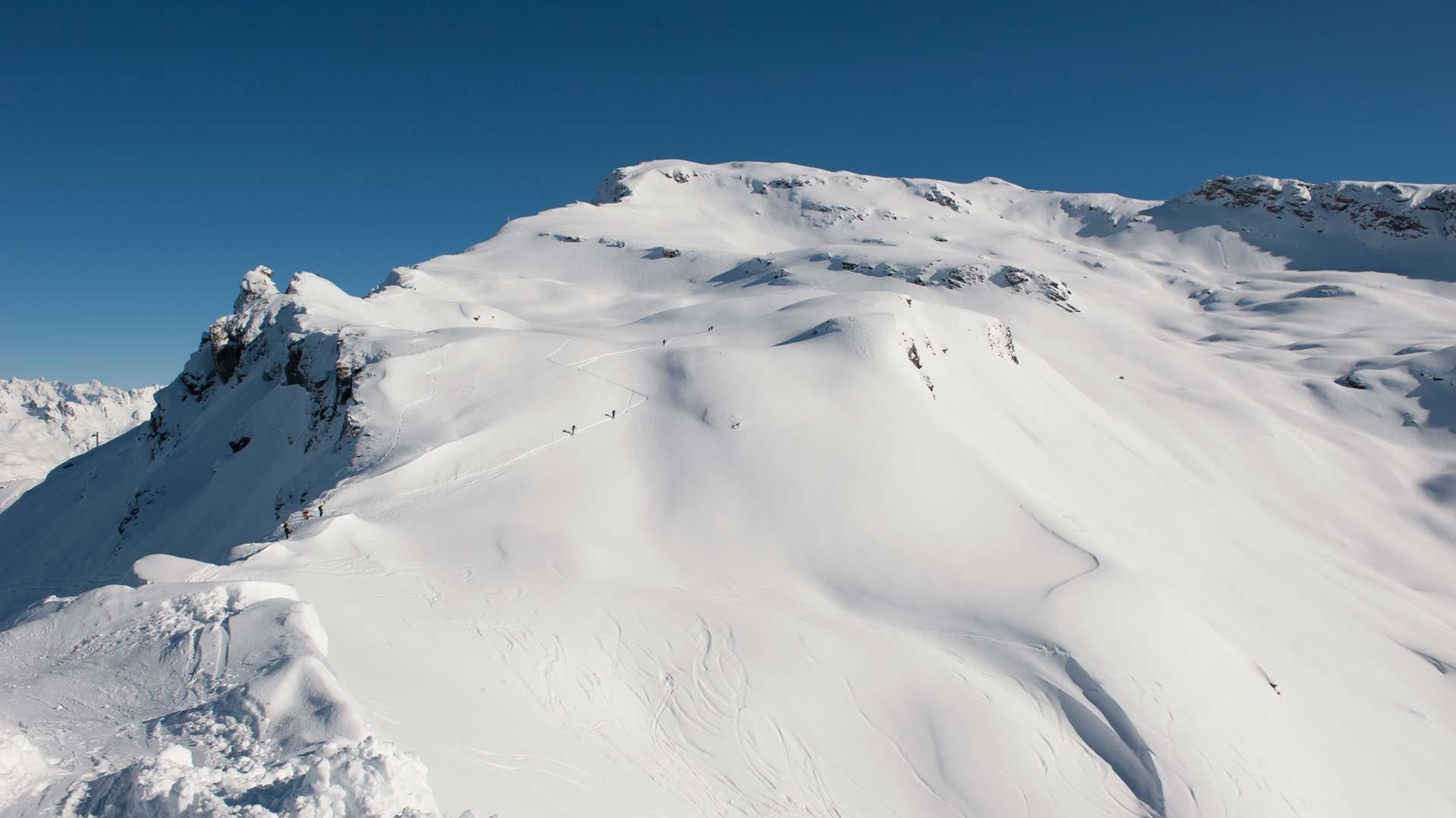 Skiers hiking to the top of Fogliettaz in Sainte Foy